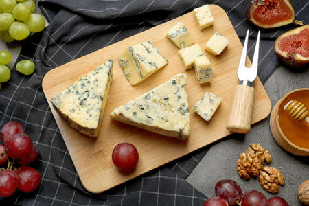 FLat lay composition with board of delicious blue cheese on table
