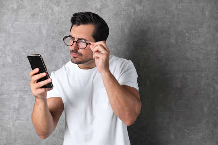 Young man with glasses using mobile phone on grey background. Vision problem