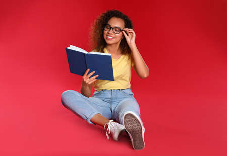 Beautiful African-American young woman reading book on red background