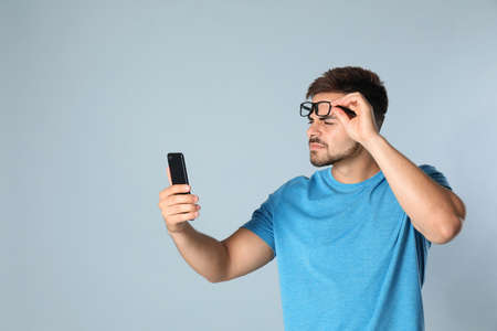 Young man with vision problems using smartphone on grey background, space for text