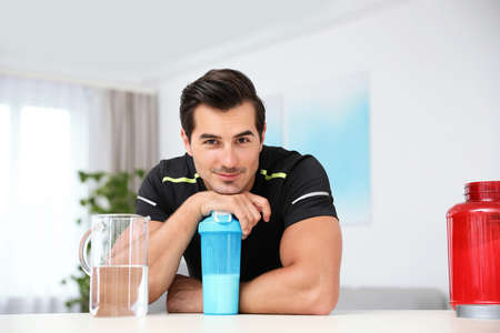Young athletic man with protein shake at home Stok Fotoğraf