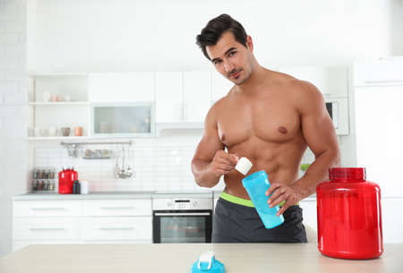 Young shirtless athletic man preparing protein shake in kitchen, space for text Stok Fotoğraf