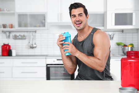 Young athletic man with protein shake powder in kitchen, space for text Reklamní fotografie - 129175559