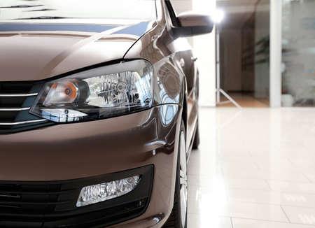 New luxury car in modern auto dealership, closeup