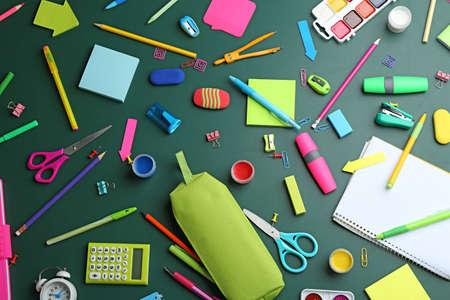 Diversi cancelleria scolastica brillante su sfondo verde, piatta Archivio Fotografico
