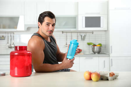Young athletic man with ingredients for protein shake in kitchen, space for text Stok Fotoğraf
