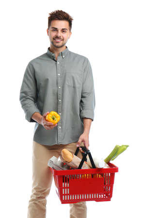 Young man with bell pepper and shopping basket full of products isolated on white Standard-Bild - 129175760
