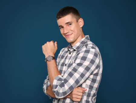 Portrait of handsome young man on blue background Imagens