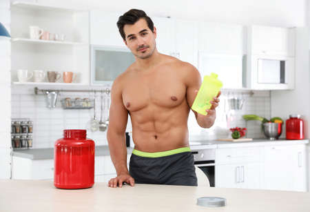 Young shirtless athletic man with protein shake powder in kitchen Stok Fotoğraf