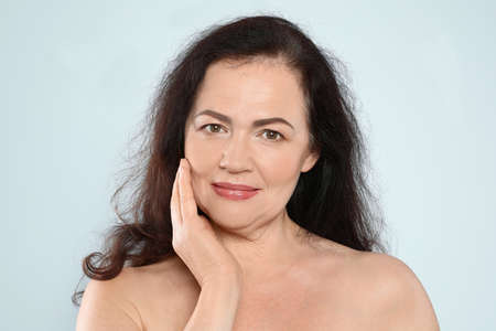 Portrait of mature woman with beautiful face on grey background Standard-Bild - 129175769