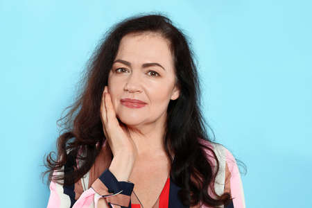 Portrait of mature woman with beautiful face on light blue background Standard-Bild - 129175787