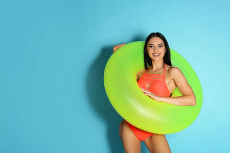 Beautiful young woman in stylish bikini with green inflatable ring on light blue background. Space for text 写真素材