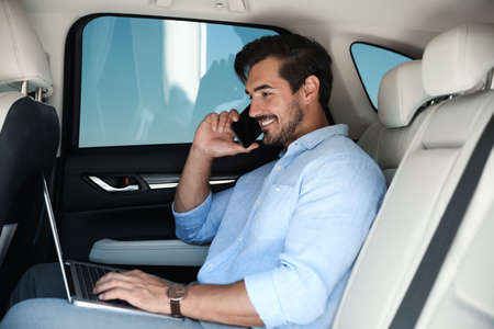 Attractive young man working with laptop and talking on phone in luxury car