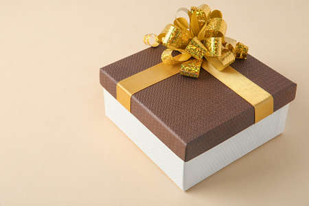 Beautiful gift box with bow on beige background