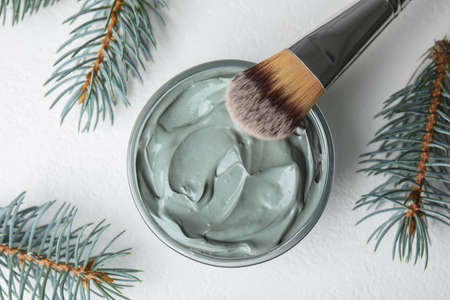 Professional face mask with spruce and brush on white table, flat lay