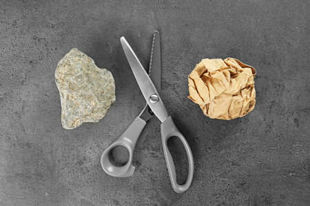 Flat lay composition with rock, paper and scissors on grey stone background