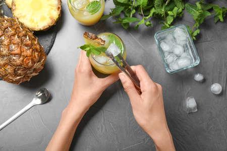 Frau setzt Eis in Glas mit Cocktail am grauen Tisch, Ansicht von oben Standard-Bild