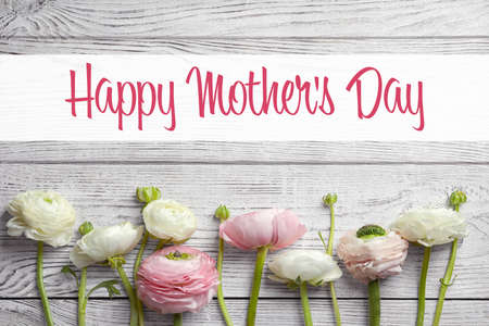 Beautiful ranunculus flowers and text Happy Mothers Day on wooden background, top view