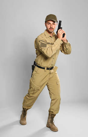 Male security guard in uniform with gun on grey background