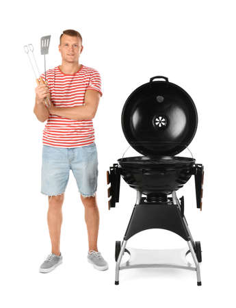 Man with barbecue grill and utensils on white background