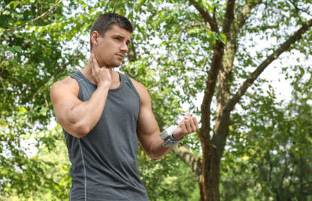 Young man checking pulse with medical device after training outdoors Фото со стока