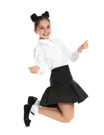 Happy girl in school uniform jumping on white background 免版税图像