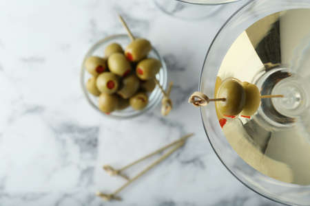 Flat lay composition with glass of Classic Dry Martini and olives on white marble table Фото со стока