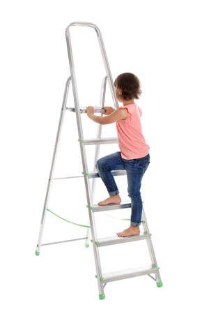 Little girl climbing up ladder on white background. Danger at home 免版税图像