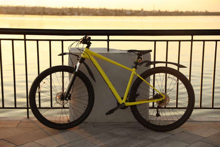 Yellow bicycle parked near railing on city waterfront at sunset Stock fotó