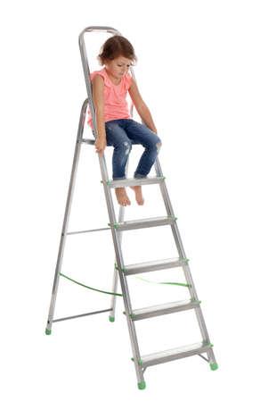 Bambina salendo la scala su sfondo bianco. Pericolo in casa