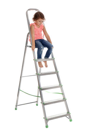 Kleines Mädchen, das Leiter auf weißem Hintergrund hinaufklettert. Gefahr zu Hause