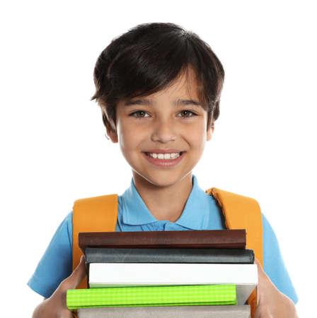 Glücklicher Junge in Schuluniform mit Stapel Büchern auf weißem Hintergrund Standard-Bild