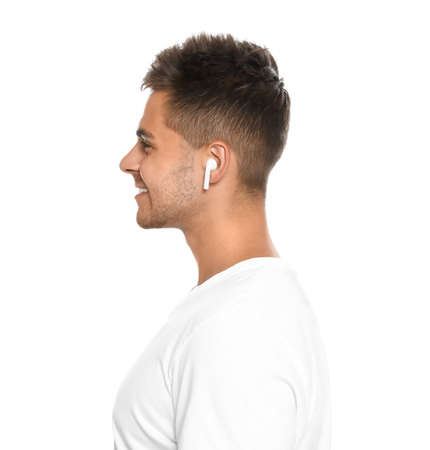 Happy young man listening to music through wireless earphones on white background Stock Photo - 129247349