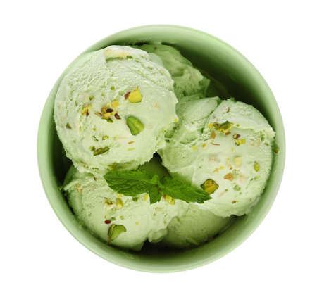 Bowl of delicious pistachio ice cream with mint on white background, top view