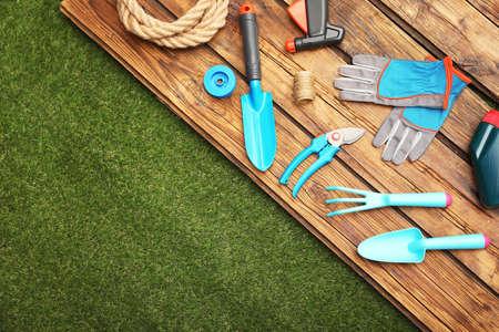 Superficie in legno con attrezzi da giardinaggio su erba verde, distesi piatti. Spazio per il testo Archivio Fotografico