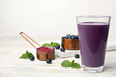 Tasty acai drink in glass, berries and powder on white wooden table Stock Photo