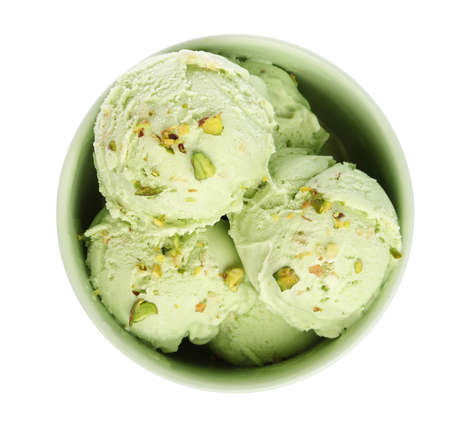 Bowl of delicious pistachio ice cream on white background, top view