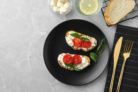 Tasty fresh tomato bruschettas on grey marble table, flat lay