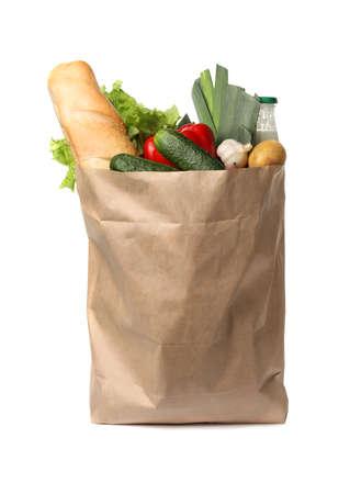 Bolsa de papel con verduras frescas y pan sobre fondo blanco.