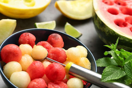 Bowl of melon and watermelon balls with scoop on table, closeup