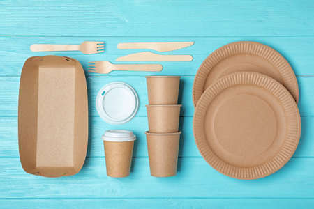 Flat lay composition with new paper dishware on light blue wooden background. Eco life