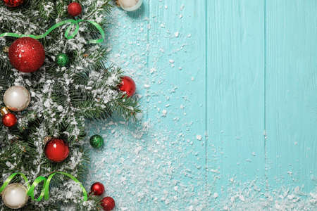 Flat lay composition with fir branches, Christmas decoration and snow on light blue wooden background. Space for text Stock Photo