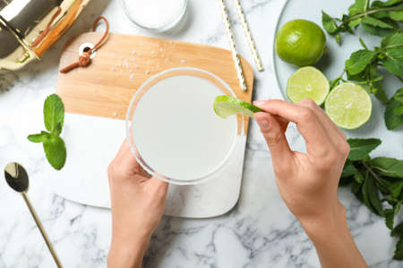Woman decorating freshly made cocktail with lime at white marble table, top view