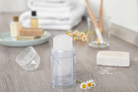 Natural crystal alum deodorant and chamomile flowers on wooden table