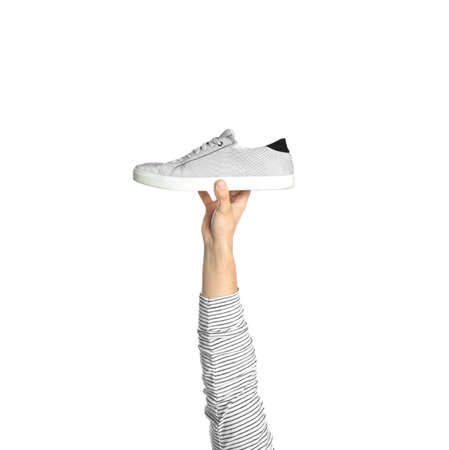 Young man holding comfortable shoe on white background, closeup