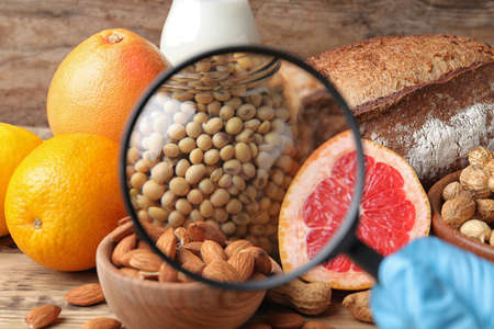 Different products with magnifier focused on jar of soy, closeup. Food allergy concept Stock Photo