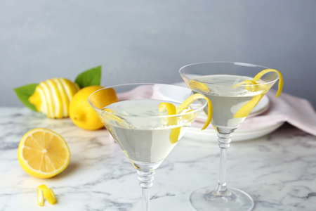Glasses of lemon drop martini cocktail with zest on marble table against grey background
