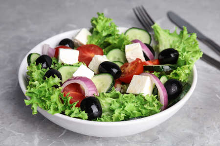 Tasty fresh Greek salad on grey marble table, closeup