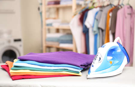 Modern electric iron and folded clothes on board in laundry room. Space for text Banque d'images