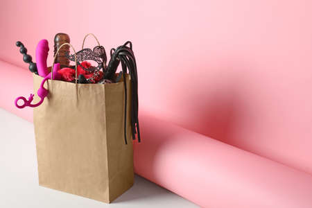 Paper shopping bag with different toys on pink background. Space for text